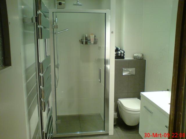 de nw. inloopdouche met muurtje tus toilet en douche